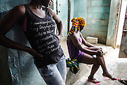 Lucie, 15 (left), and Nicole , 16, in the entrance of the brothel where they work in Abidjan, Cote d'Ivoire on Wednesday July 17, 2013.