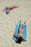 Portuguese Summer. Two women enjoy the sun at Carcavelos beach in outskirts of Lisbon.