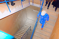 Tour guide wearing  shiny blue overalls is leading the way down at the stairs at the Werdhölzli Sewage Treatment Plant, Zürich, Switzerland.