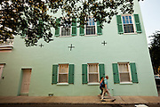 Couple blurred walk past Rainbow row historic houses along Battery Street Charleston, SC.