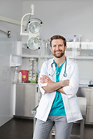 Portrait of smiling veterinary doctor standing with arms crossed at clinic