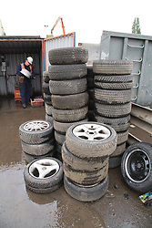 Pile of car tyres which are waiting to have the aluminium wheel salvaged at a metal recycling centre,
