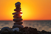 Pyramide of rounded stones by the sea at sunset