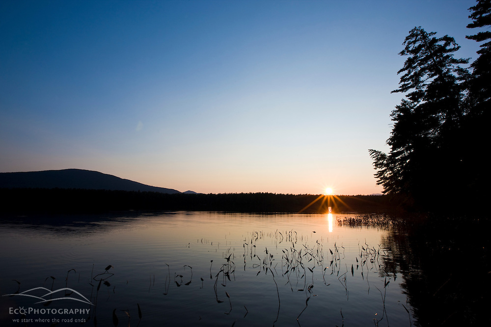 The sun sets over White Lake at White Lake State Park in Tamworth, New Hampshire.