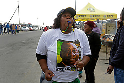 Wednesday 8th May 2019.<br /> Monwabisi Park, Harare,<br /> Khayelitsha, Cape Town, <br /> Western Cape, <br /> South Africa.<br /> <br /> SOUTH AFRICAN GENERAL ELECTIONS 2019!<br /> <br /> SOUTH AFRICAN PROVINCIAL AND NATIONAL ELECTIONS 2019! <br /> <br /> An ANC supporter wears ANC colours and blows a blue whistle as she and other ANC supporters dance and sing political songs together outside the voting station as others stand in a queue in the background waiting to cast their vote at Monwabisi Park, Harare in Khayelitsha near Cape Town, Western Cape, South Africa.<br /> <br /> Registered South African Voters head to the various IEC (Independent Electoral Commission) Voting Stations where they are registered to vote as they cast their votes and take part in voting and other activities on Voting Day 8th May 2019 during the South African General Elections 2019. Voters from across the nation stood in queue's along with many others to vote in the Provincial and National Elections being held in South Africa on Wednesday 8th May 2019.   <br />  <br /> Copyright © Mark Wessels. All Rights Reserved. No Usage Without Permission.<br /> <br /> PICTURE: MARK WESSELS. 08/05/2019.<br /> +27 (0)61 547 2729.<br /> mark@sevenbang.com<br /> studioseven@mweb.co.za<br /> www.markwesselsphoto.com