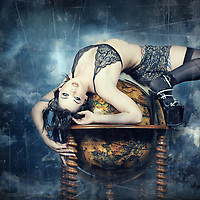 A dark haired woman in black and gold lingerie, stockings, and heels lays draped across an antique globe. The globe floats amongst clouds, supported by carved wooden columns.