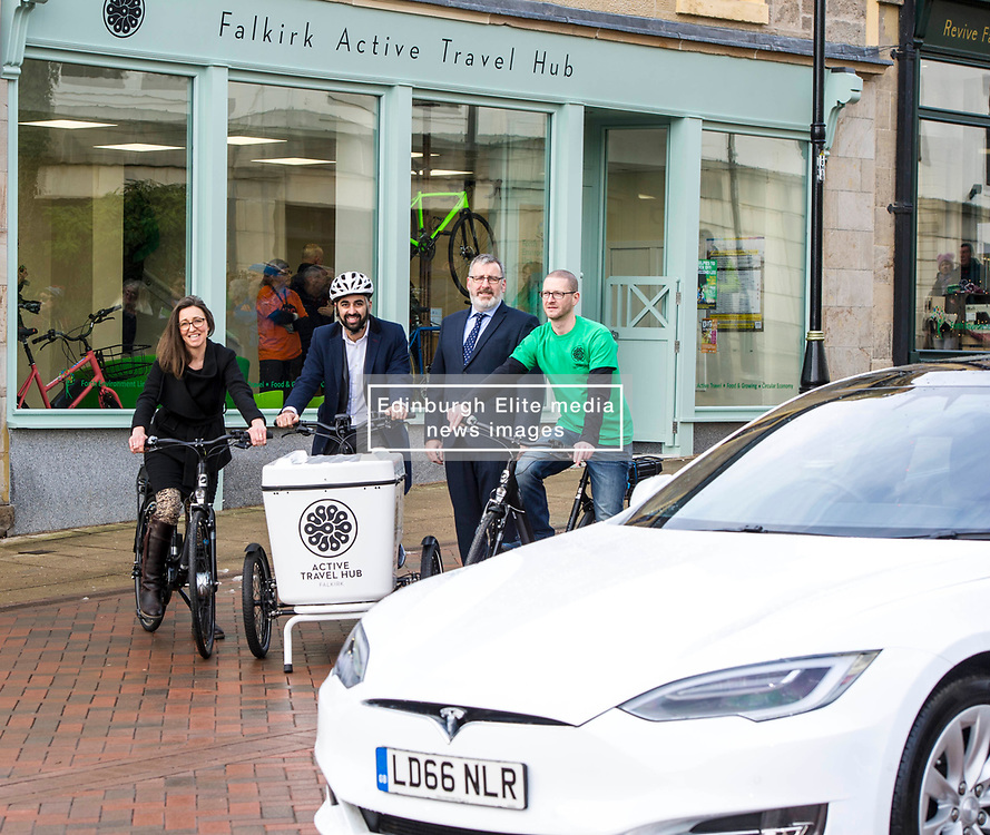 Pictured: Clara Walker, Forth Environment Link Chief Executive, Humza Yousaf, Pete Reid, Growth & Investment Manager and Ray Burr, Falkirk Active Travel Hub Coordinator get on the bikes next to a Tesla electric car<br /> Transport minister Humza Yousaf MSP opened Falkirk's active travel hub. The resource will encourage people to make healthier, greener travel choices. <br /> <br /> <br /> Ger Harley | EEm 6 February 2018