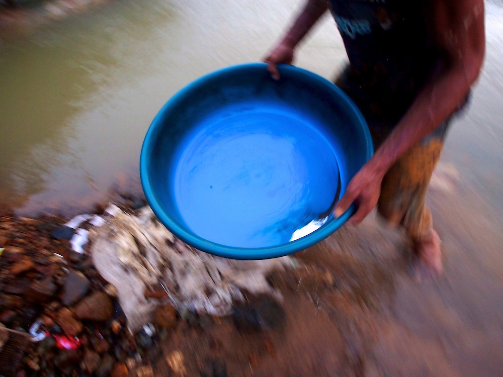 """Young boys process gold using plastic tubs and mercury along the banks of the Guinobatan River outside the town of Aroroy.  A liquid sludge, made by tumbling gold ore and water in mechanized tumblers, is mixed with mercury then  """"panned.""""  The sludge is discarded but the mercury is retained.  Forcing the mercury through a nylon sieve made from remnants of a common umbrella produces a 1/4-inch amalgam pellet.  The amalgam is then heated with an oxygenated gasoline torch to a temperature sufficient to evaporate the mercury revealing pure gold.  ..During the process, some mercury is inevidably spilled and leaches into rivers, streams and groundwater. ..While mines process ore, another miner washes his hair...A pan containing the mercury used to process liquified gold ore...Story Summary:.Small-scale gold mining in the Philippines uses mercury and cyanide to extract elemental gold from ore extracted from mines and pits dug by hand.  Very young children, some as young as four, are put to work at less dangerous but still rigorous tasks in the gold mining areas.  These include panning in streams or rivers and hauling ore sacks that can weigh up to 60 pounds.  Children often play near mechanized equipment and highly toxic mercury and cyanide.  These chemicals, used to help extract elemental gold from ore, are leached into nearby watersheds where fish and other marine life, mainstays of the Philippine diet, are poisoned.  The high price of gold and the poor economy in many developing countries has led to an increase in small-scale gold mining throughout the world."""