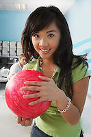 Young woman at bowling alley holding ball portrait