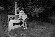 """Village of Cayuga resident Alicia Maywalt, whoo was helping to oversee a neighbor's collection of goods for sale during the annual """"50 Mile Yardsale"""" sets out an old highway sign to help draw attention to the property, Saturday, July 30, 2016 along Route 90 in the Cayuga Lake region of the Finger Lakes, New York."""