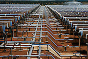 """La Dehesa, 50 MW parabolic through solar thermal power plant with molten salts storage. Completed in February 2011, it is located in La Garovilla (Badajoz), Spain, and it is owned by Renovables SAMCA. With an annual production of 160 million kwh, La Dehesa will be able to cover the electricity needs of more than 45,000 homes, preventing the emission of 160,000 tons of carbon. The 220 h plant has 225,792 mirrors arranged in rows and 672 solar collectors wich occupy a total length of 100km."""",""""- solar field formed by the fluid and the fluid circulation system."""
