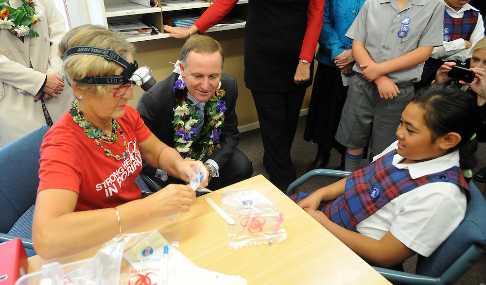Prime Minister John Key watches as Public Health Nurse Annie Highet swabs a child for Rheumatic Fever after an announcement of testing at seven area schools, at the Holy Family School, Porirua, New Zealand, Wednesday, May 09, 2012. Credit:SNPA / Ross Setford