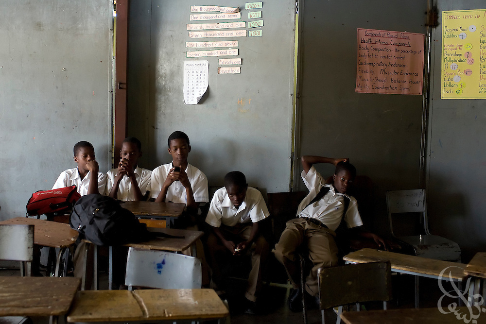 Jamaican schoolboys seem more interested in cell phone texting than their lessons as they sit in the rear of a classroom in the Mountain View area of Kingston, Jamaica December 10, 2008. As violence has spiraled out of control in Jamaica over the past several years, it has also increasingly reported in schools across the country.