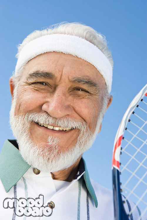 Senior man holding tennis racket, portrait
