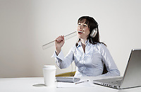 Woman with earphones fooling around at desk