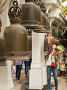 "12 JULY 2014 - PHRA PHUTTHABAT, SARABURI, THAILAND: People ring prayers bells before the Tak Bat Dok Mai at Wat Phra Phutthabat in Saraburi province of Thailand. Wat Phra Phutthabat is famous for the way it marks the beginning of Vassa, the three-month annual retreat observed by Theravada monks and nuns. The temple is highly revered in Thailand because it houses a footstep of the Buddha. On the first day of Vassa (or Buddhist Lent) people come to the temple to ""make merit"" and present the monks there with dancing lady ginger flowers, which only bloom in the weeks leading up Vassa. They also present monks with candles and wash their feet. During Vassa, monks and nuns remain inside monasteries and temple grounds, devoting their time to intensive meditation and study. Laypeople support the monks by bringing food, candles and other offerings to temples. Laypeople also often observe Vassa by giving up something, such as smoking or eating meat. For this reason, westerners sometimes call Vassa ""Buddhist Lent.""<br />     PHOTO BY JACK KURTZ"