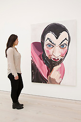 © Licensed to London News Pictures. 19/11/2013. London, UK. A Saatchi Gallery employee views 'Faust' (2008), an oil painting of the character by American artist Amy Bessone, at the press view for 'Body Language' a new exhibition at the gallery in London today (19/11/2013). Focussing on the human form, the exhibition features the work of 19 emerging international artists and opens to the public on the 20th of November 2013. Photo credit: Matt Cetti-Roberts/LNP
