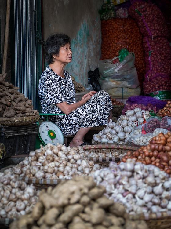HANOI, VIETNAM - CIRCA SEPTEMBER 2014:  Portrait of Vietnamese woman selling vegetables in the streets of Hanoi, Vietnam.