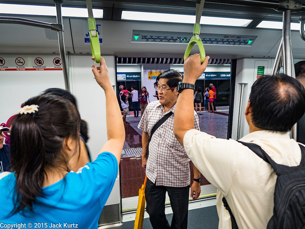 """27 DECEMBER 2015 - SINGAPORE, SINGAPORE: Passengers ride the expanded Downtown Line on the first day of service on the new line. Singapore opened the extension of the Downtown Line on its subway system Sunday. The extension is a part of Singapore's plans to make the city-state a """"car lite"""" metropolis with plans to double the current subway to more than 360 kilometers of track by 2030. The government plans to have 80% of homes within a 10 minute walk of a subway station.    PHOTO BY JACK KURTZ"""