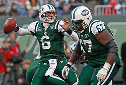 Nov 29, 2009; East Rutherford, NJ, USA; New York Jets offensive tackle Damien Woody (67) blocks while New York Jets quarterback Mark Sanchez (6) throws a pass during the second half at Giants Stadium. The Jets defeated the Panthers 17-6.