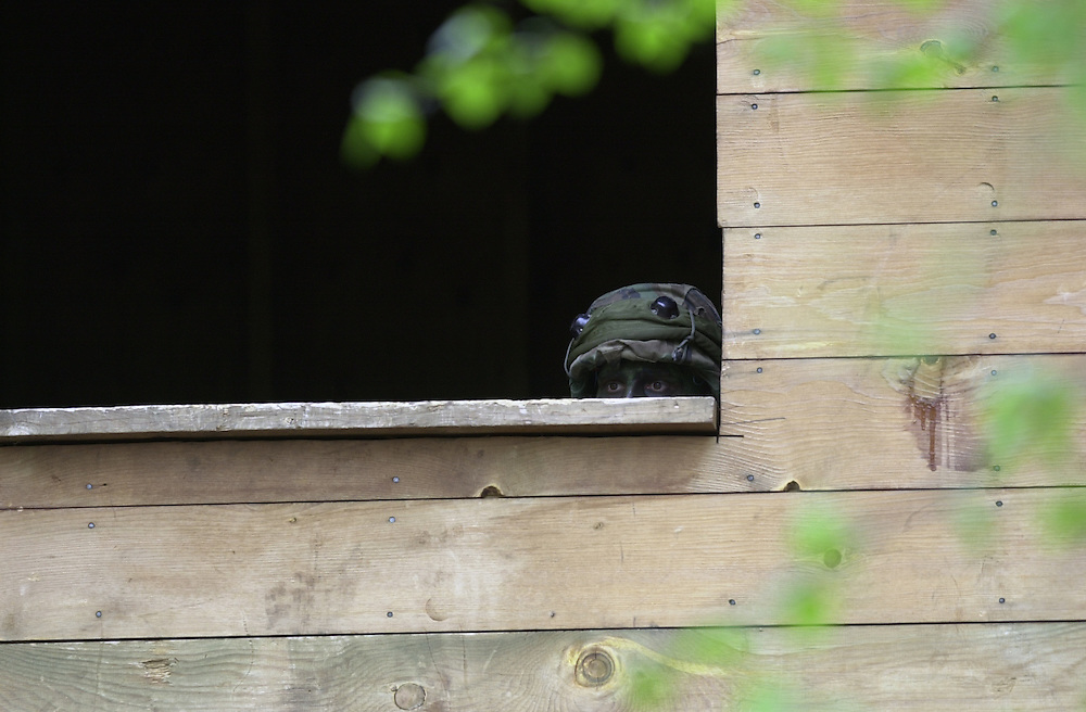 A national guard soldier looks out a window for attackers during urban assault training at Camp Ripley, in Minnesota.