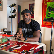 BALTIMORE, MD - FEB23: Chris Wilson, 38, a business owner in Baltimore, in his apartment in Bolton Hill in Baltimore, MD, where he paints about criminal justice.  Wilson went to prison at age 17 for murder, but got his associates degree while in prison and was able to attend the University of Baltimore after his release. He testified in Annapolis about the ban the box movement in Maryland which would remove the question about a person's criminal history from college applications.(Photo by Evelyn Hockstein/For The Washington Post)