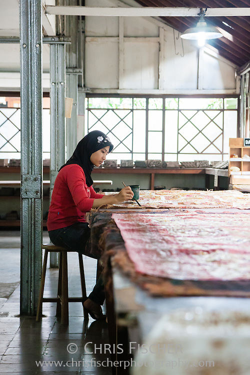 Making batik - Indonesian woman brown coloring the parts from which the wax has been scraped off. Plentong, Yogyakarta, Central Java, Indonesia.