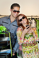 Happy young man carrying boxes while woman text messaging in fashion boutique