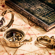 Antique brass compass on a very old navigation map with an antique logbook and a ship' brass hook