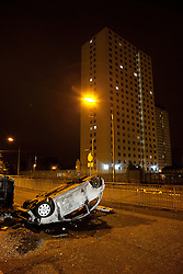 © Licensed to London News Pictures. 10/08/2011. Salford, UK. An upturned and burned out car in the road. Scenes of desctruction around Salford Precinct in Greater Manchester, where people rioted and looted. Photo credit : Joel Goodman/LNP