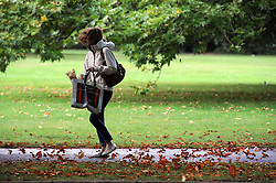 © Licensed to London News Pictures. 24/09/2014<br /> Autumn leaves blowing around this lady.<br /> A sunny autumn day in Greenwich Park,Greenwich,London. (today 24.09.2014)<br /> (Byline:Grant Falvey/LNP)