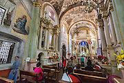 Worshipers inside the Sanctuary of Atotonilco with Mexican folk Baroque murals painted on the ceiling and walls in Atotonilco, Mexico. The paintings were done by Antonio Martinez de Pocasangre and Jose Maria Barajas over a period of thirty years and is known as the Sistine Chapel of Mexico.
