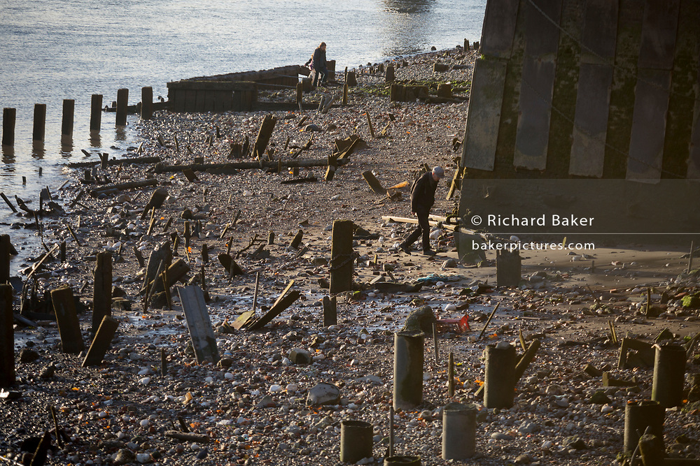 "A mudlarker looks for historical items lying in the mud and silt of the river Thames at low tide, on 30th October 2017, at Queenhithe, the City of London, England. Queenhithe is also the name of the ancient, but now disused, dock which derives from the ""Queen's Dock"", or ""Queen's Quay"", which was probably a Roman dock (or small harbour). The dock existed during the period when the Wessex king, Alfred the Great, re-established the City of London, circa 886 AD."