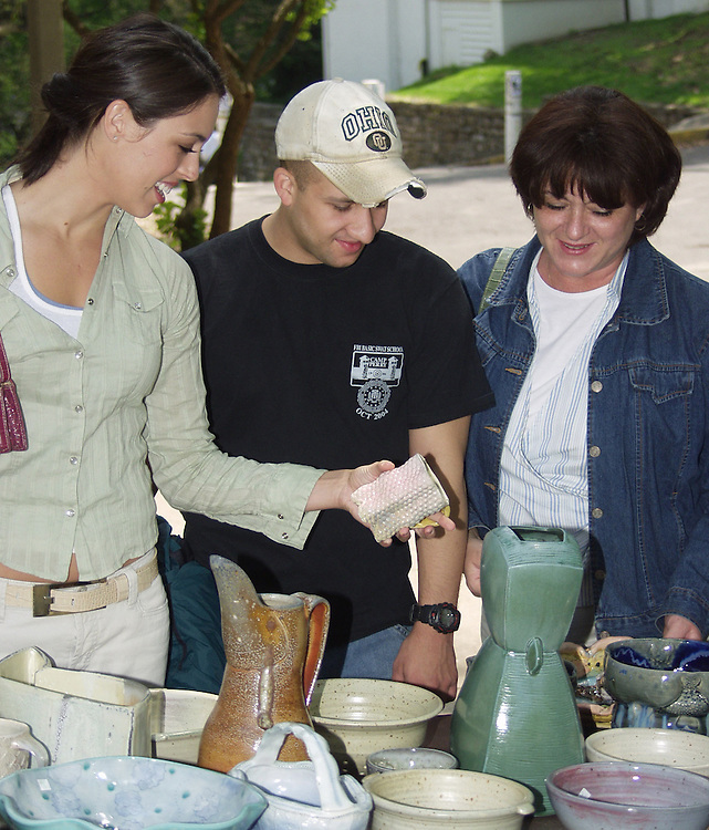Elise Haeuptle, her mother Mary Haeuptle and Christian Cullen browse through the pottery on sale by graduate art students in front of Trisolini Gallery Saturday afternoon.
