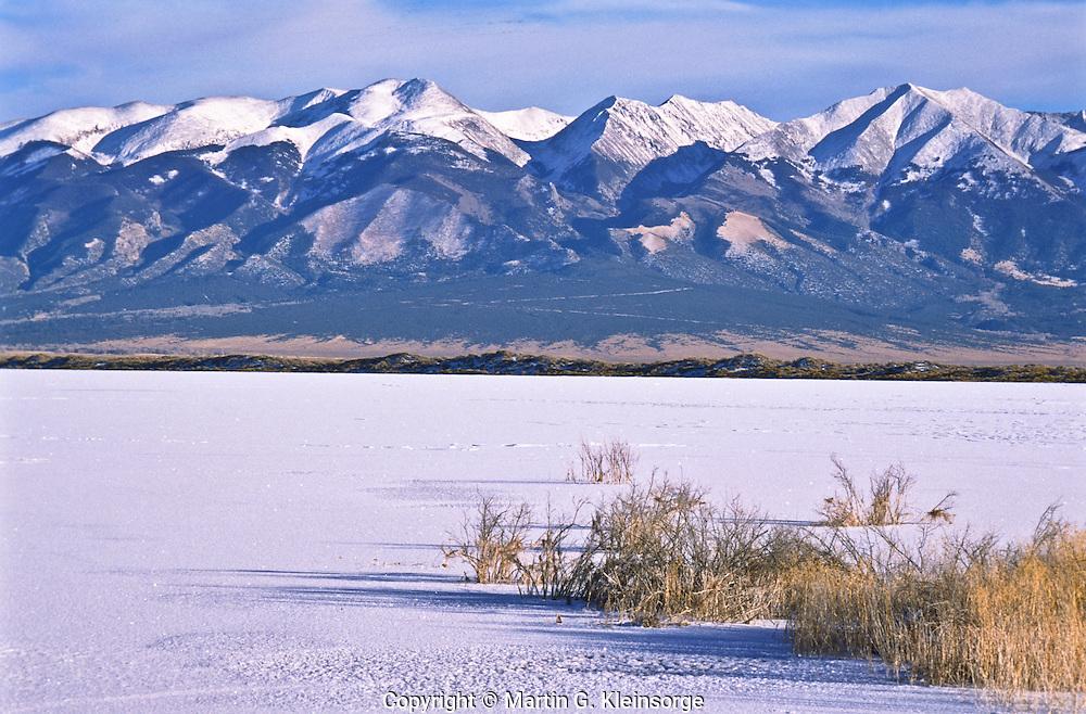 A frozen San Luis Lake at San Luis State Park with the Sangre DE Cristo Mountains in the distance.  Colorado.