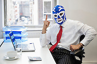 Portrait of businessman in wrestling mask points up at office desk