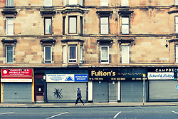 Closed shops with shutters down below tenement apartments on Victoria Road in Govanhill district of Glasgow, Scotland, United Kingdom