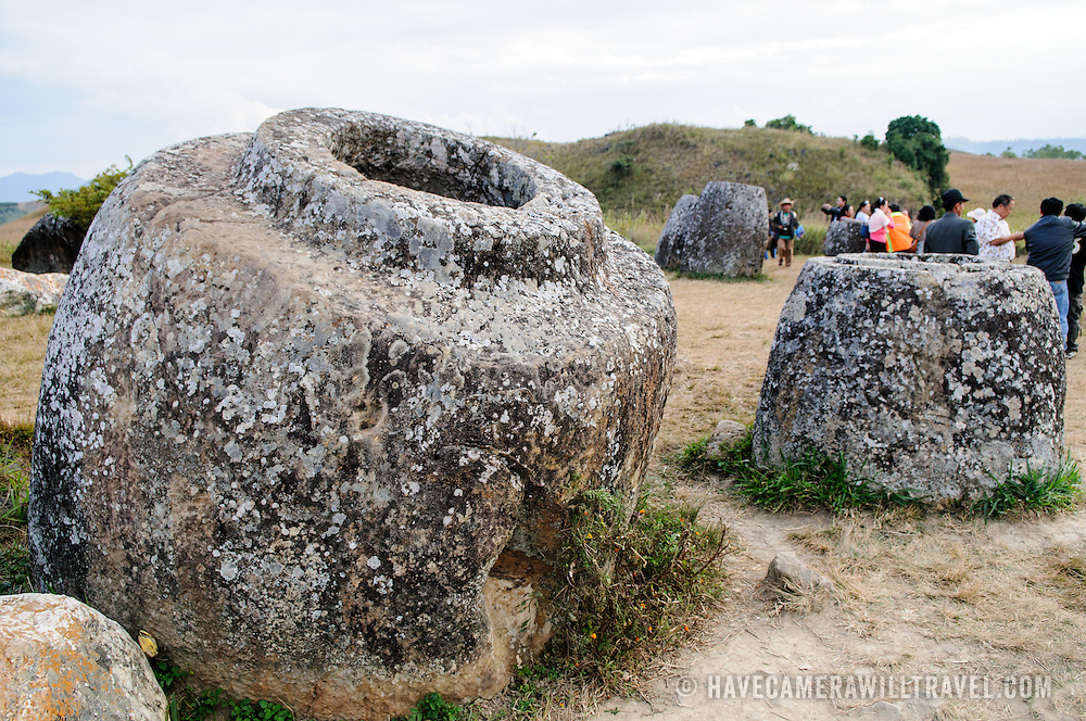 A group of tourists amongst the stone jars at Site 1 of the Plain of Jars in north-central Laos. Much remains unknown about the age and purpose of the thousands of stone jars clustered in the region. Most accounts date them to at least a couple of thousand years ago and theories have been put forward that they were used in burial rituals.