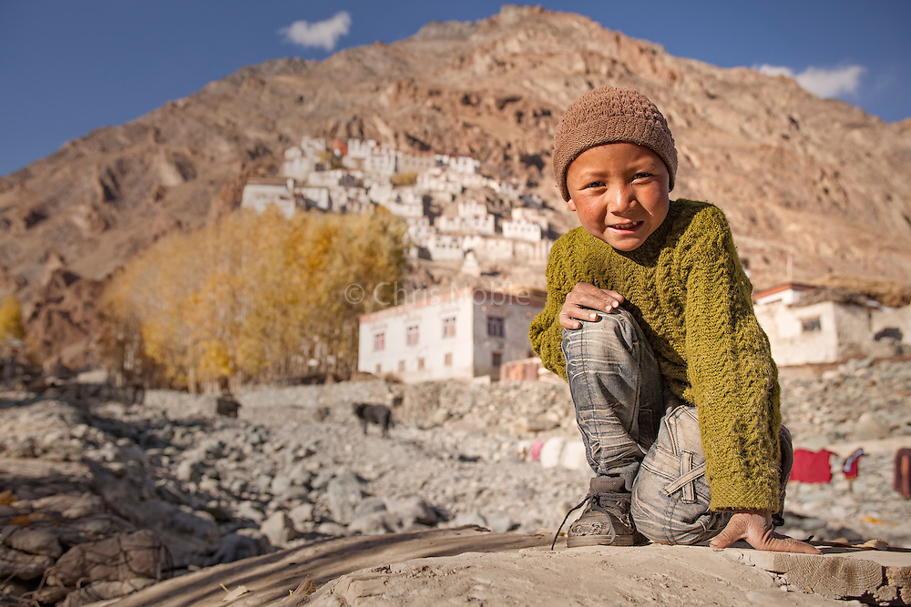 A young boy kneels before Karsha Monastery in the Zanskar Valley of Ladakh India.