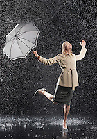 Woman standing on one leg holding umbrella leaning into falling rain