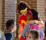 Dr. Elizabeth Law hugs a student while dressed up like the superhero, Wonder Woman, at Duncan Creek Elementary during the first day of school on Tuesday in Mill Creek. All of the Duncan Creek staff dressed up as a superhero to calm the student's nerves as they returned back to school. (Staff Photo: David Welker)
