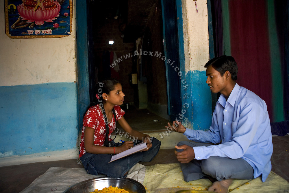 Pooja, 14, a student from the village of Pathpuri, Hoshangabad, Madhya Pradesh, India, taking part to the children's journal, a project launched by Dalit Sangh, an NGO which has been working for the uplift of scheduled castes for the past 22 years, is interviewing a young villager in his home. Dalit Sangh is working in collaboration with Unicef India to promote education and awareness within backward communities.