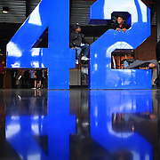 Young baseball fans play on Jackie Robinson's number 42 sculpture inside the entrance to Citi Field during the New York Mets V San Francisco Giants Baseball game at Citi Field, Queens, New York. 21st April 2012. Photo Tim Clayton