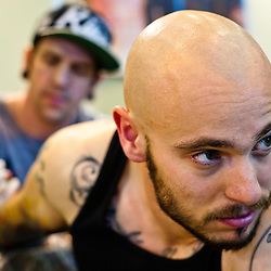 Manchester, UK - 4 August 2012: a visitor is tattooed on his arm during the Manchester Tattoo Show, one of the most popular conventions of the UK tattoo community.