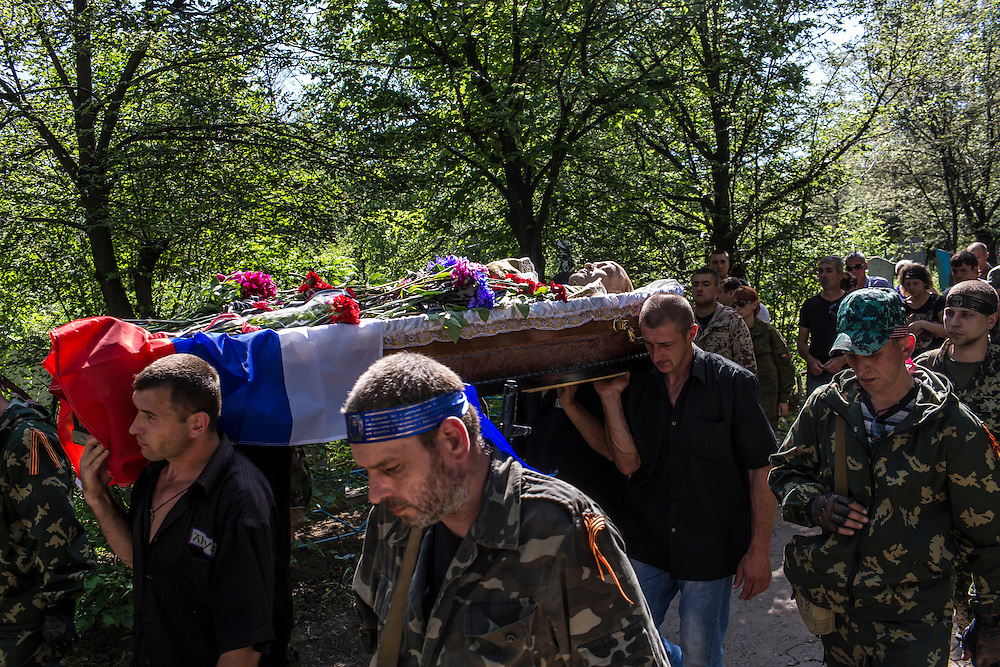 HORLIVKA, UKRAINE - MAY 24: A casket containing the body of Aleksandr Politov, a pro-Russia militia fighter who was killed when his group attacked a Ukrainian military checkpoint two days earlier in the village of Blahodatne, is carried through the cemetery before his burial on May 24, 2014 in Horlivka, Ukraine. Presidential elections are scheduled for tomorrow, but pro-Russia militias have been seeking to prevent them from being administered throughout the eastern part of the country. (Photo by Brendan Hoffman/Getty Images) *** Local Caption ***