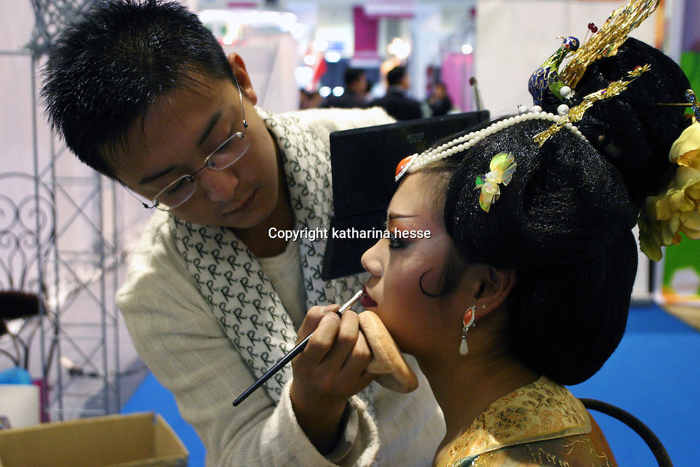 BEIJING, 22. October 2004 : a Chinese woman gets a traditional Chinese make up from a professional at the International Beauty Week in Beijing, October 22, 2004, in China. Beauty business is booming in China. Sales in beauty related businesses and products are worth more than 7 billion USD last year.      ..Whereas in Mao Zedong's China, even pigtails were seen as a sign of vanity (and had to be cut off) , nowadays, urban Chinese women seek about every means in order to distinguish themselves from the masses.  This year Beijing will organize the worl'd first beauty pageant for women had had plastic surgery in early December...