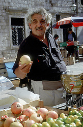 Dubrovnik:  A fruit seller welcomes a customer in the city's famous open market in Gundulic Square.