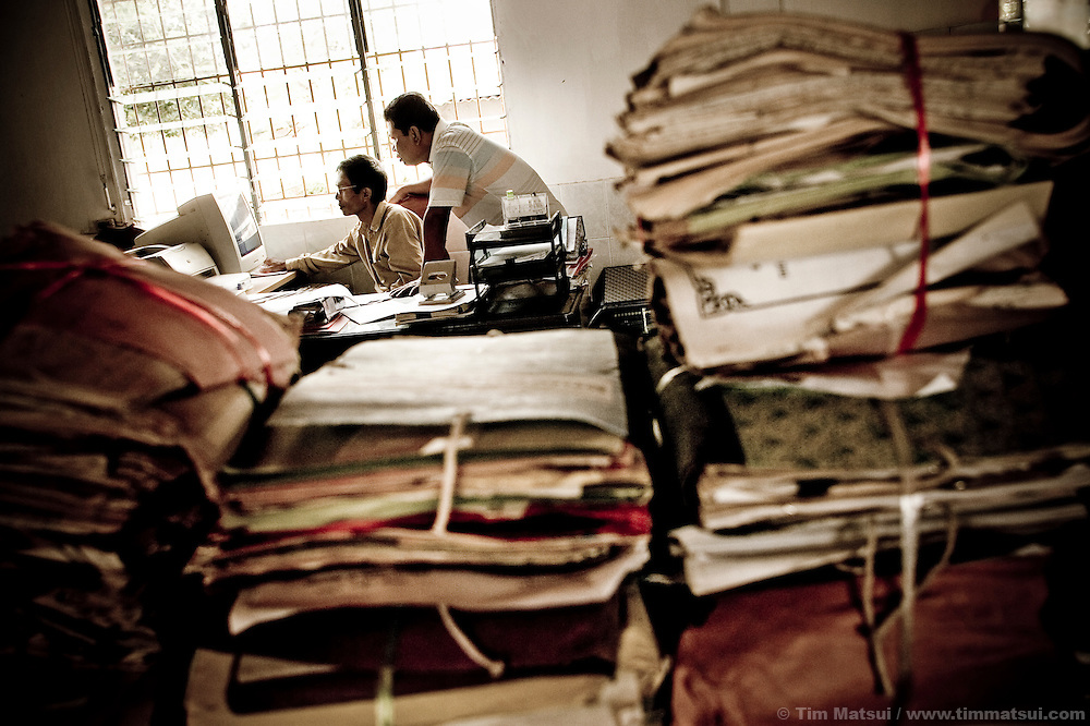 Social workers with the Ministry of Social Affairs sort through a sex trafficking victim's case prior to her reintegration to the community of Sihanoukville where her parents now live.