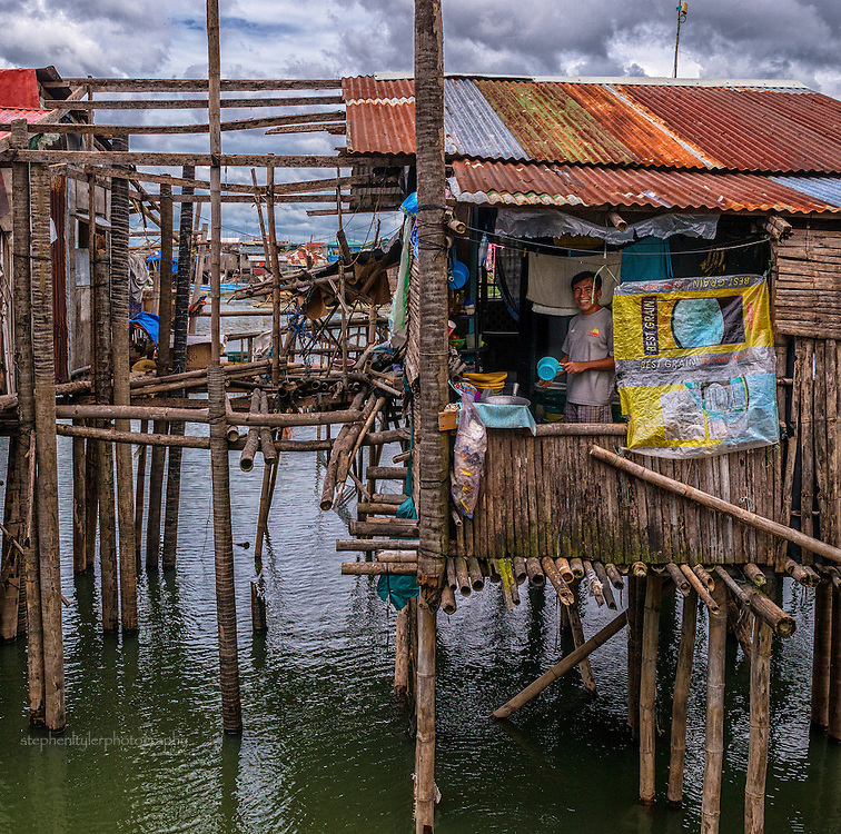 Everyday life in a fishing village community with nearly everything built from bamboo on top of stilts on the edge of a lake. A man washing up in the window of his eating area
