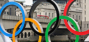 © Licensed to London News Pictures. 28/02/2012, London, UK. A red Routemaster bus seen through the rings. Giant Olympic rings measuring 11 metres high by 25 metres wide are floated down the River Thames on a barge, marking 150 days to go to the start of the London 2012 Olympic and Paralympic Games. Photo credit : Stephen Simpson/LNP